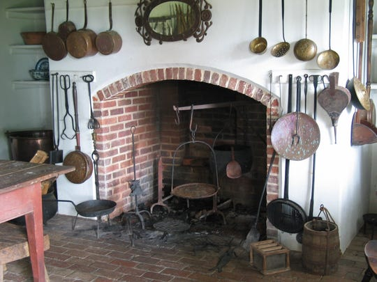 Separate colonial kitchen with implements in fireplace.