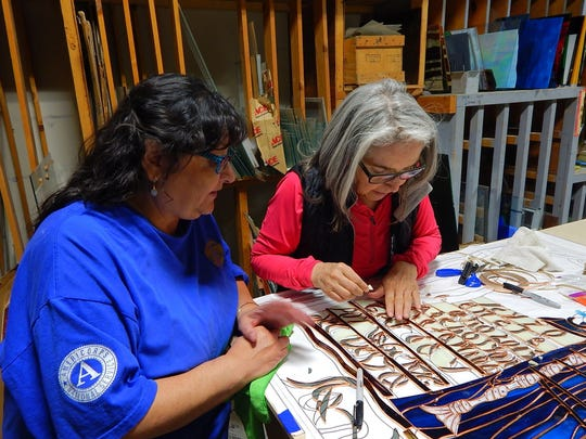In this March 3, 2016, photo provided by Carrie Leven, Cynthia Rael-Vigil, left, and Jean Rael work on a stained glass window for the historic San Antonio Catholic Church in Questa, N.M. The community will celebrate the rededication of the church with a special Mass on Sunday, Aug. 14, 2016. It took volunteers tens of thousands of hours over the last several years to rebuild the heart of one mountain village in northern New Mexico.