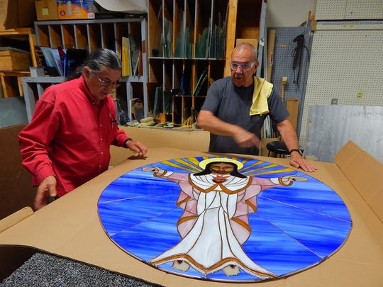 In this May 26, 2016, photo provided by Carrie Leven,  Marcus Rael and Leroy Apodaca inspect one of the handmade stained glass windows for the historic San Antonio Catholic Church in Questa, N.M. The community will celebrate the rededication of the church with a special Mass on Sunday, Aug. 14, 2016. It took volunteers tens of thousands of hours over the last several years to rebuild the heart of one mountain village in northern New Mexico.