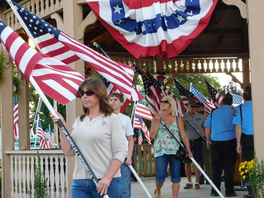 Volunteers pick up a flag and carry it to its resting place for a 24-hour display at the Clyde Gazebo.