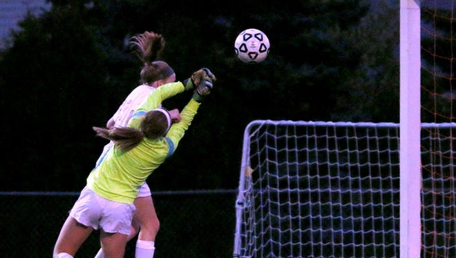 Northville goalkeeper Emily Maresh punches the ball away from a would-be Salem scorer.
