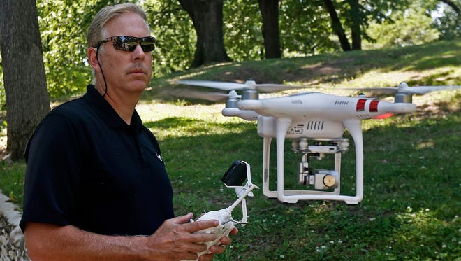 In this June 9, 2017 photo, Jim Robesky hovers his DJI Phantom drone at eye level with  the remote control, at Parker Heights Park in Quincy, Ill. The drone has a small video/still camera below which he can view from his phone with the downloaded app. Drones, also known as unmanned aerial vehicles or UAVs, are a hot item right now. The Consumer Technology Association said about 2.8 million drones were sold in the United States last year.