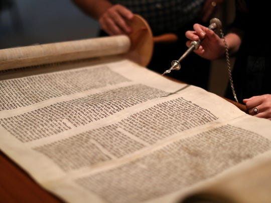 Rabbi Jack Romberg of Temple Israel helps his student with a Torah reading.