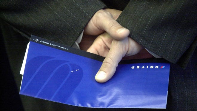 A passenger holds his ticket while waiting to board a United Airlines flight at San Francisco International Airport.