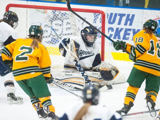 Essex goalie Victoria Gibson, center, makes a point-blank save against BFA-St. Albans' Elena Brigham (18) during the third period of Saturday's game.