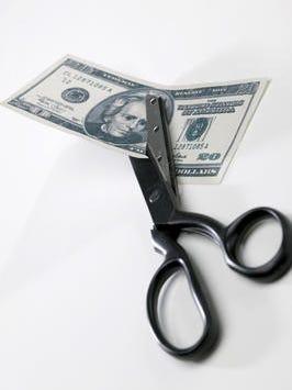 Scissors cutting through twenty dollar bill budget cut trim