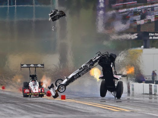 NHRA top fuel dragster driver Larry Dixon (right) crashes