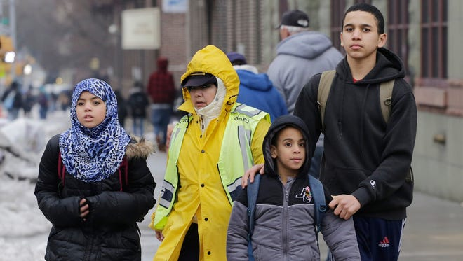 A crossing guard assists three Muslim school children at the end of a school day March 4, 2015 in the Brooklyn borough of New York. Mayor Bill de Blasio announced that schools will close for two Muslim holidays starting in September.