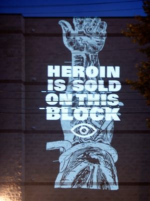 """""""This message is relevant to any block,"""" artist Adam DelMarcelle said while projecting his latest art work on a building at Willow and N 6th Street. DelMarcelle projected the words, """"Heroin is sold on this block"""" Tuesday night, Aug. 16."""