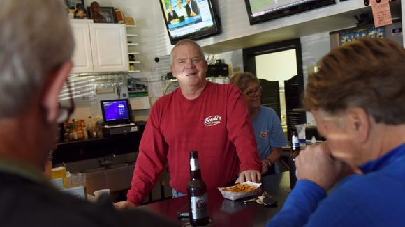 Jon Bot (center), owner of Botski's Bar and Grill, talks with regulars during happy hour on Friday.