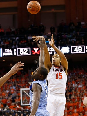 Virginia Cavaliers guard Malcolm Brogdon (15) shoots the ball over North Carolina Tar Heels forward Theo Pinson (1) in the second half at John Paul Jones Arena. The Cavaliers won 79-74.