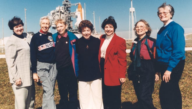 """Seven members of the First Lady Astronaut Trainees (FLATs, also known as the """"Mercury 13""""), pose for a photograph outside Launch Pad 39B near the Space Shuttle Discovery in 1995. From left: Gene Nora Jessen, Wally Funk, Jerrie Cobb, Jerri Truhill, Sarah Rutley, Myrtle Cagle and Bernice Steadman."""