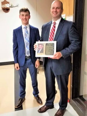 Darryl Volpicelli, right, receives the Distinguished Graduate Hall of Fame plaque from Logan Roberts, president of the Groton High School National Honor Society,