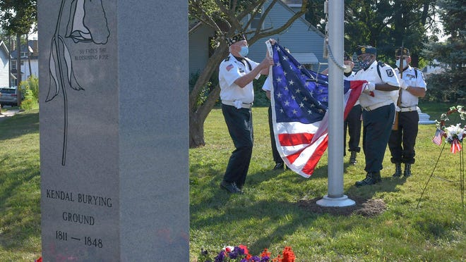 Members of American Legion Post 221 in Massillon raise the flag at the Kendal Burying Ground pole dedication and flag-raising ceremony on Saturday.