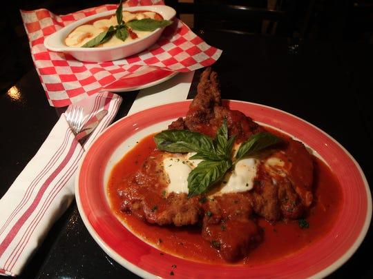 Gnocchi Sorrentina homemade potato pasta, top, and veal chop parmigiana, served at Parm Centro Restaurant.