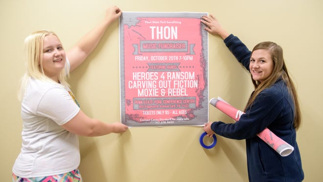 Penn State students Casey Dierdorff, left, primary chair for Penn State York Benefiting THON, and Janelle Kress, publicity co-chair at York, hang signs to promote the upcoming benefit concert for THON.