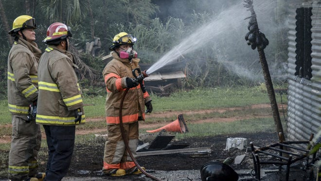 Pågat: Guam Fire Department firefighters douse a burned home in Mangilao on June 18. There were no reported injuries.
