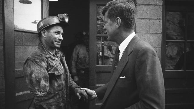 John F. Kennedy shakes hands with a one-armed miner while on the campaign trail during the primaries in April 1960 in Mullens, W. Va.