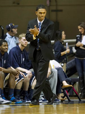 Monmouth coach King Rice walks on the sidelines during an NCAA college basketball game against West Virginia, Friday, Nov. 14, 2014, in Morgantown, W.Va. (AP Photo/Raymond Thompson)