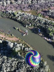 A hot air balloon flies near the San Juan River during the San Juan River Balloon Rally on Friday.