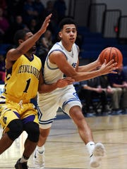 Phillip Williams looks to make a pass to the wing during the second half of Zanesville's 63-61 loss to visiting Reynoldsburg on Saturday at Winland Memorial Gymnasium.