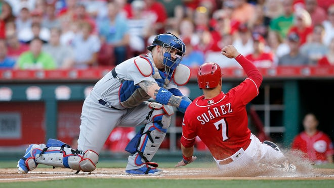 Cincinnati Reds third baseman Eugenio Suarez (7) is tagged out at the plate by Los Angeles Dodgers catcher Yasmani Grandal (9) as Jose Peraza reaches first on a fielder's choice in the bottom of the second inning at Great American Ball Park on Friday, June 16, 2017.