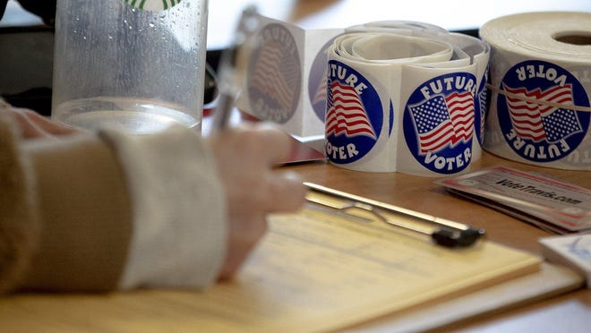 Madelyn Martinez registers to vote at Austin Community College's Eastview Campus on Jan. 29 in Austin.