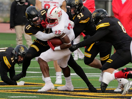 St. John's wide receiver Evan Clark is stopped for a short gain by the Wisconsin-Oshkosh defense during the Johnnies' 31-14 loss to the Titans in the second round of the Division III playoffs Saturday afternoon at Titan Stadium in Oshkosh, Wis.