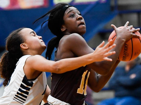 Central's Hya Haywood drives to the basket under pressure from Reitz's Kyla Terry as the Central High School Bears play the Reitz High Panthers at Reitz High School Thursday, December 15, 2016.