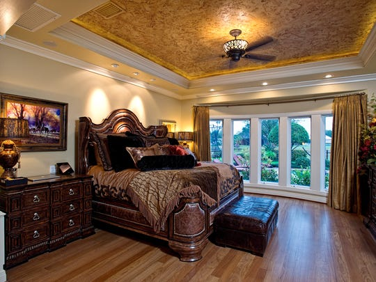 The master bedroom is floored in hardwood and features intricate crown molding and a custom painted recessed ceiling.