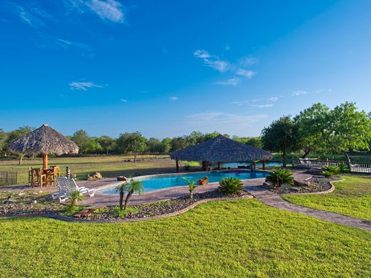 A tropical Paradise in the backyard features a huge pool 6.5' deep with a Baja shelf for sunning, a swim up bar, under the palapa with a sunken outdoor kitchen.