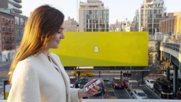 A woman walking past a Snapchat billboard.