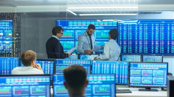 Stock traders in a room with lots of screens.