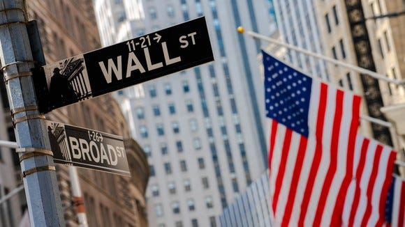 Street signs marking the intersection of Wall Street and Broad Street, with American flags hanging from the New York Stock Exchange.