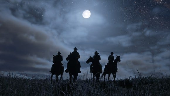 "Four cowboys on horseback on a moonlit night in a screenshot from recently released videogame ""Red Dead Redemption 2."""