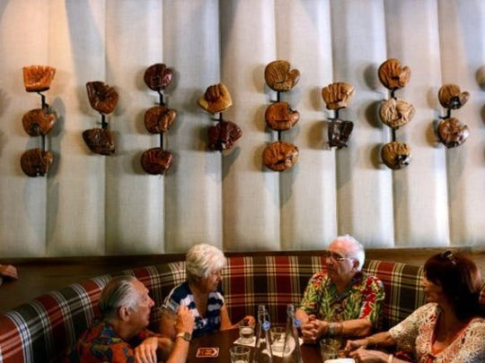Diners chat near a display of vintage baseball gloves