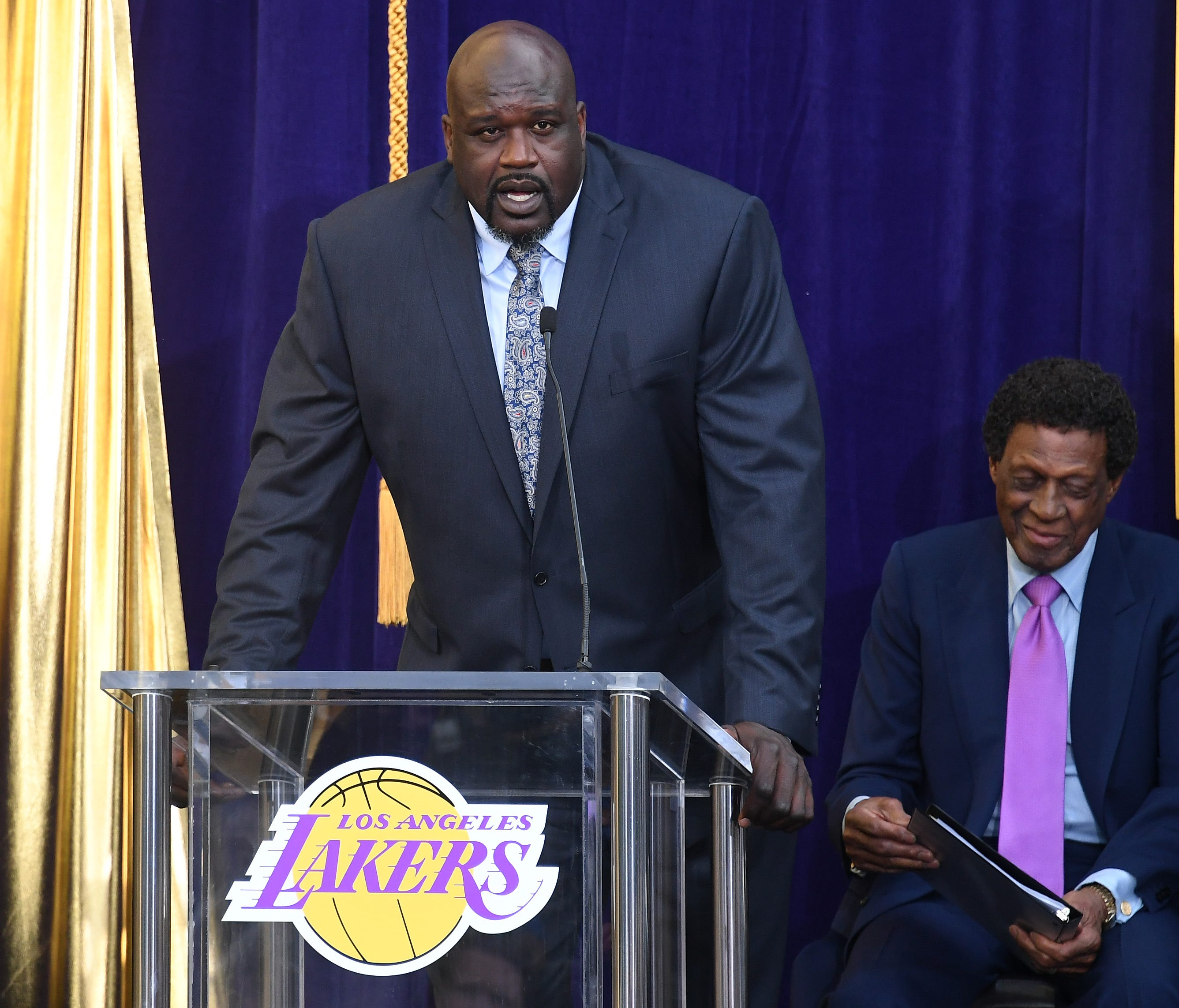 Former Los Angeles Lakers player Shaquille O'Neal (L) speaks during a statue unveiling for former player Elgin Baylor (R) prior to the game between the Los Angeles Lakers and the Minnesota Timberwolves at Staples Center.