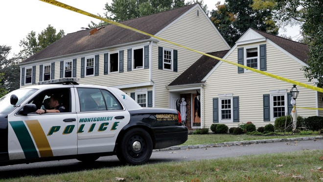 A Montgomery Township police officer sits in front of a partially burned home on Meadow Run Drive early Monday, Sept. 29, 2014, in Montgomery Township, N.J. John Sheridan, 72, the president of a major southern New Jersey hospital, and his 69-year-old wife, Joyce were killed when a fire broke out in their home.