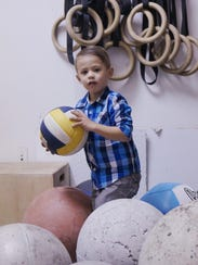 Two-year-old Landon Carignan plays in Dad's crossfit