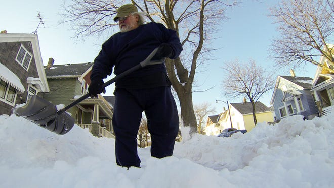 Bob Sam shovels his sidewalk in Milwaukee on Monday. Milwaukee set a snowfall record for Feb. 1, with a total of 10.4 inches, according to the National Weather Service.