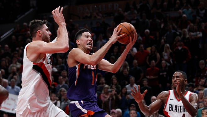 Phoenix Suns guard Devin Booker, center, shoots as Portland Trail Blazers center Jusuf Nurkic, left, and forward Maurice Harkless, right, defend during the second half of an NBA basketball game in Portland, Ore., Saturday, Oct. 28, 2017. The Trail Blazers won 114-107.
