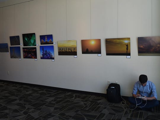 A traveler is seen resting at the Burning Man, Through the Artist's Lens photo exhibit at the Reno-Tahoe Airport on Aug. 13, 2015.