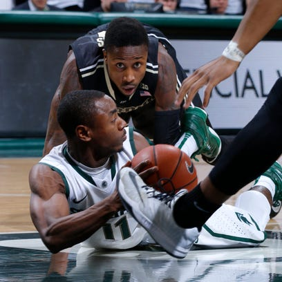 Michigan State's Lourawls Nairn Jr. (bottom) and Purdue's Jon Octeus scramble for a loose ball during the first half Wednesday night at Breslin Center.