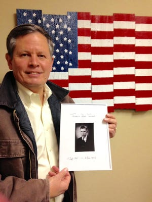 Sen. Steve Daines holds a picture of his great-uncle Thomas Dee Tarbet.
