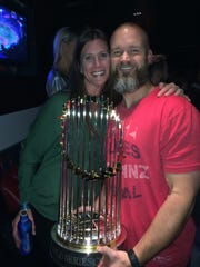 Boston Red Sox catcher David Ross, with wife Hyla, holds the World Series trophy in 2013.