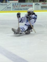 Norris Foster competing in sled hockey.