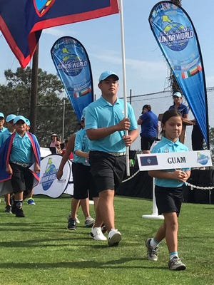 Brentt Salas carries the flag for Guam at the opening of the IMG Junior World Golf Championship in Torrey Pines, SD.