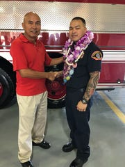 Mr. A.C. Sablan congratulates John Vincent Chaco upon his graduation from Cycle One of the Fire Academy on Dec. 15 held at Fire Station One on Andersen Air Force Base. The Andersen Fire and Emergency Services Flight provided the 13 week training graduating ten new Firefighters.