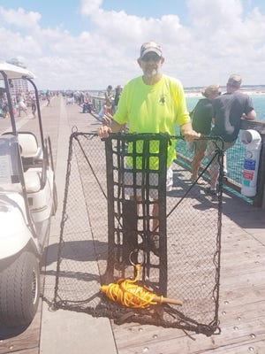 Navarre resident Ralph Agnew poses at the Navarre Beach Fishing Pier with a net he designed that will allow for easier retrieval of large sea turtles that have been hooked on a fishing line near the pier. Agnew, working with the Navarre Beach Sea Turtle Conservation Center, is trying to get a patent for the net that will be used by pier attendants who are responsible for bringing hooked sea turtles up to the pier after being notified by fisherman.
