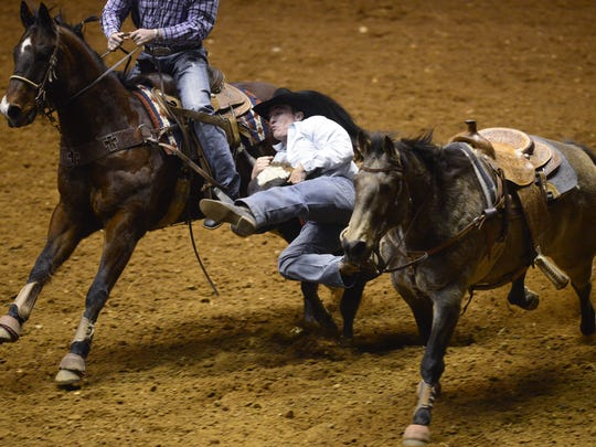 Shane Mobley competes in steer wrestling during the SLE Rodeo at Garrett Coliseum in Montgomery, Ala. on Friday March 14, 2014.